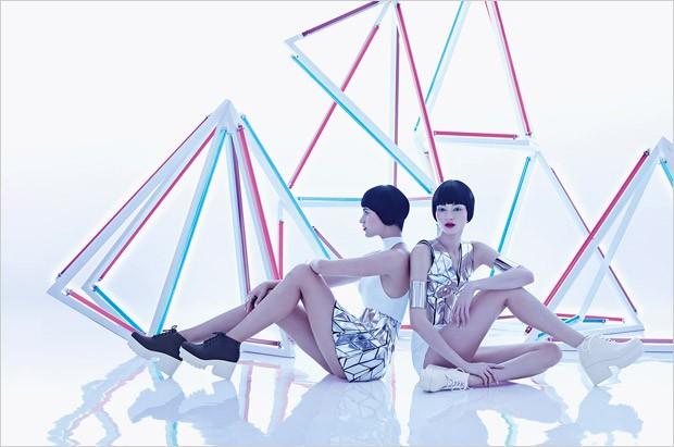 Modelos sentadas frente a instlacion de triangulos color neon
