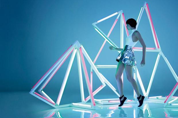 Modelo con shorts metalizados bailando en instalacion de tubos neon
