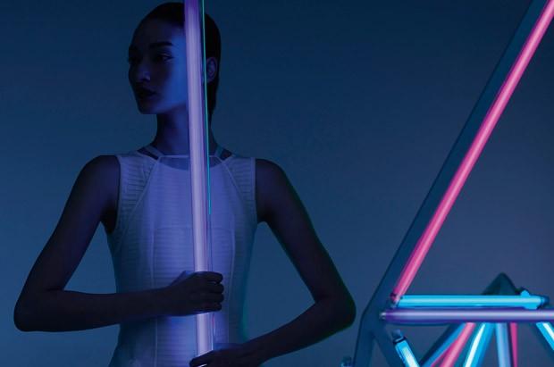Modelo con vestido blanco tocando tubo neon en la oscuridad