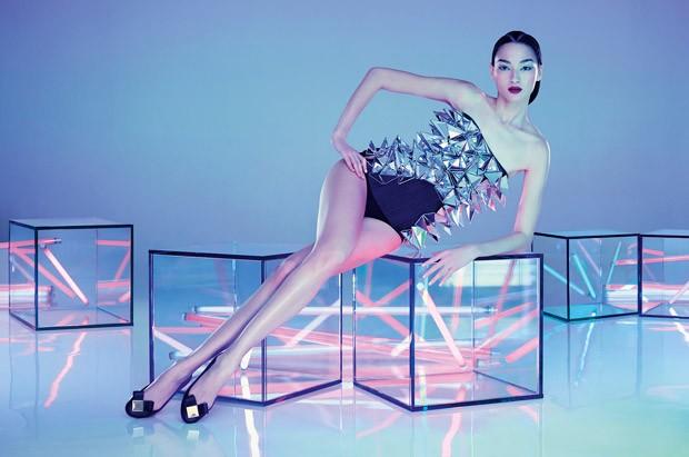 Modelo sentada en cubos transparentes con luces neon