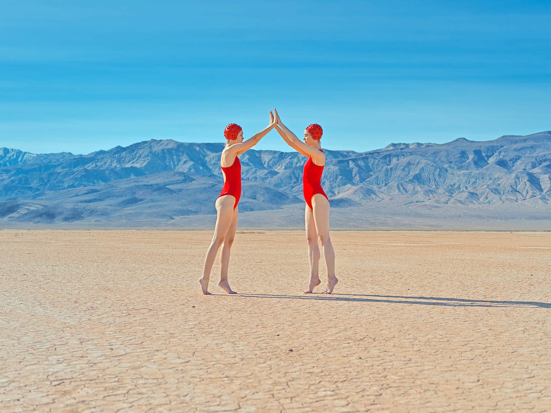 To modeller med røde badedrakter i sanden