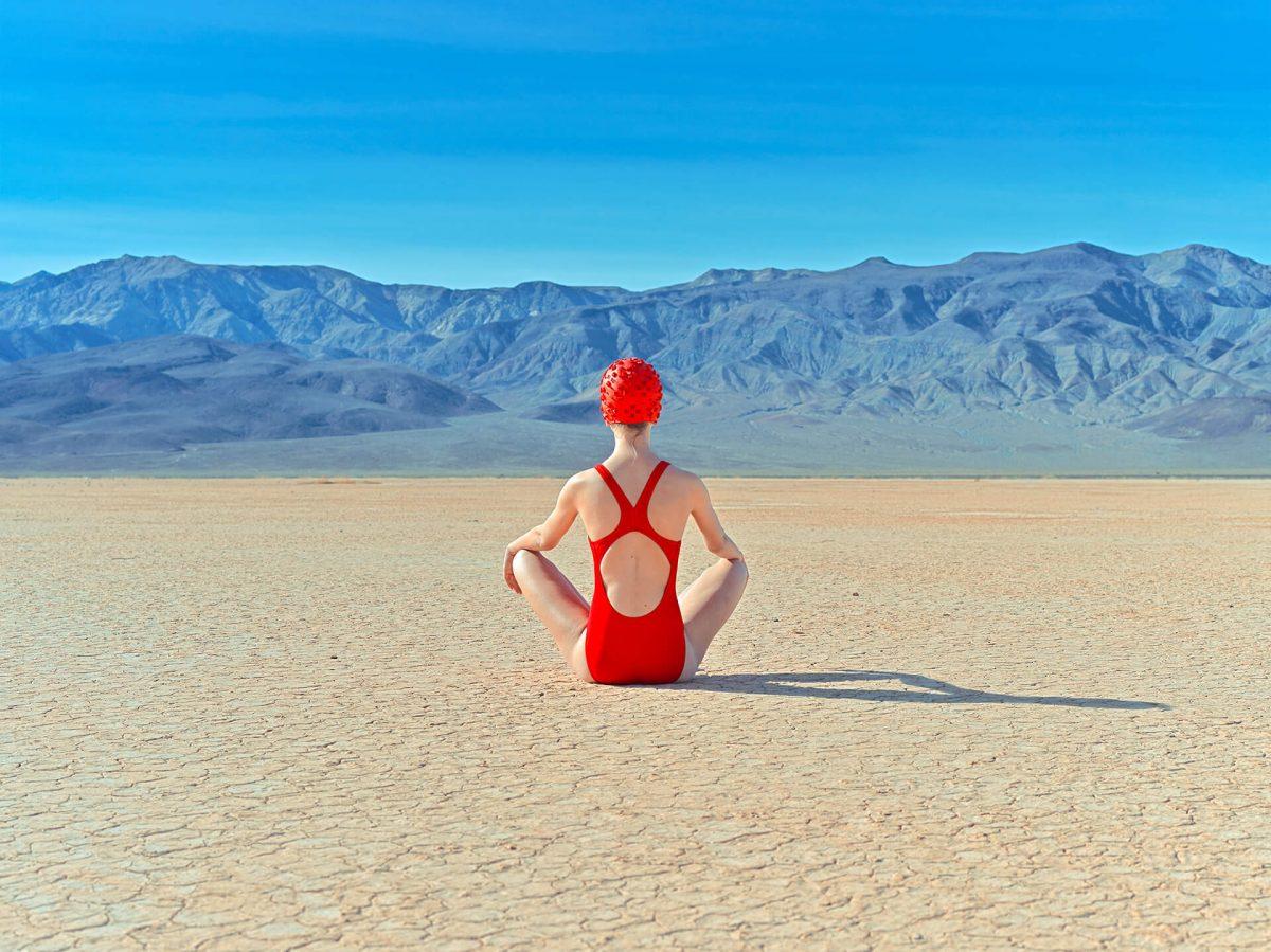 Jente med rød badedrakt sitter på sanden