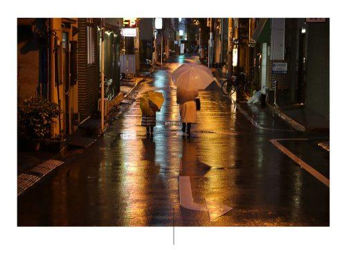 شخصان يمشيان في المطر ليلاً في اليابان