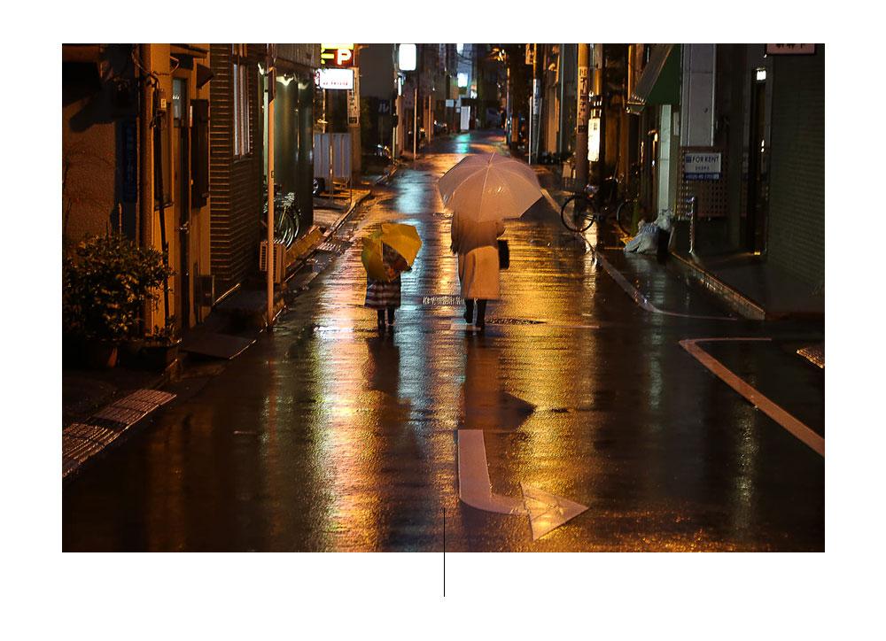 Twee mensen die in de regen bij nacht in Japan lopen